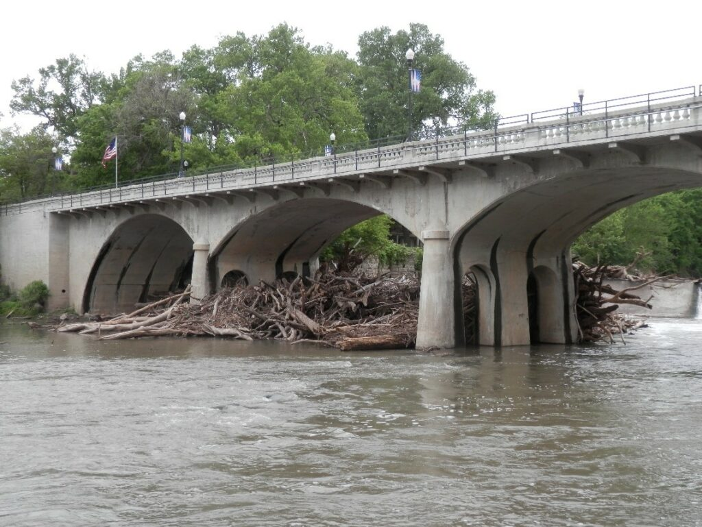 Large amounts of wood clogging the underneath of a bridge