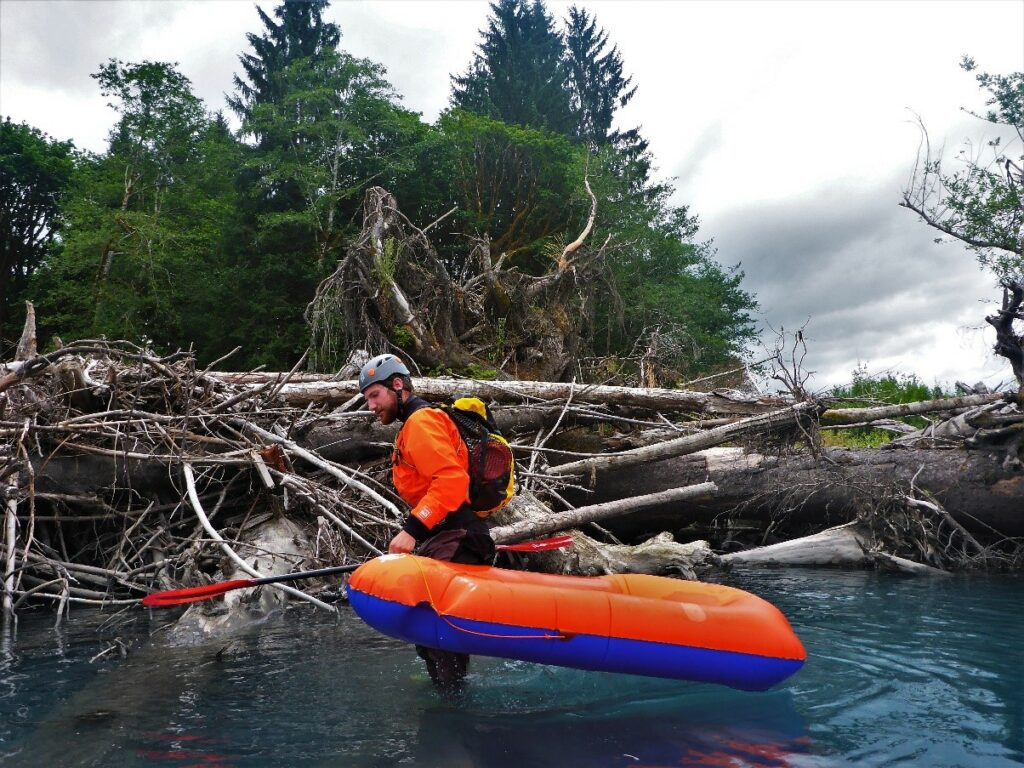 The author carrying his raft over a massive wood jam