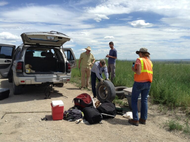 Research group changing a flat tire on a car.